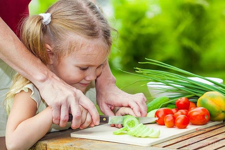 девочка режет овощи